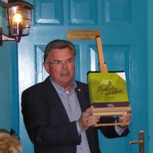 Voorzitter Frans Broos met de brochure op de schildersezel (c) margot van den boer